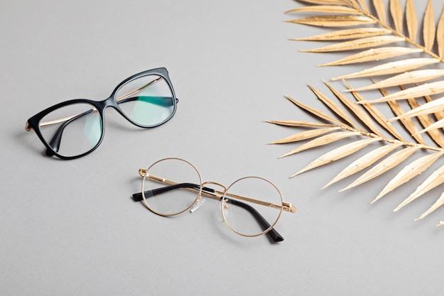 Stylowe okulary na pastelowej ścianie. sklep optyczny, dobór okularów, badanie wzroku, badanie wzroku u optyka, koncepcja akcesoriów modowych. widok z góry, płaski układ