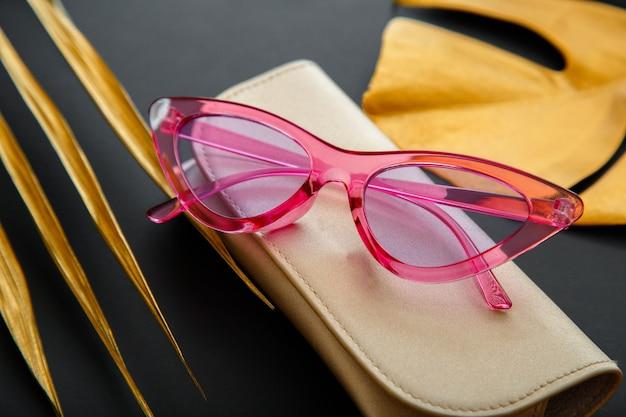 Stylowe okulary przeciwsłoneczne funky pink na ciemnym czarnym tle ze złotymi liśćmi palmowymi. letnia różowa modna optyka glamour w złotej kopercie.