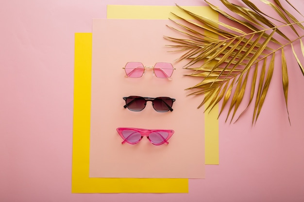 Stylowe okulary przeciwsłoneczne. jasne letnie okulary przeciwsłoneczne na różowym tle ze złotymi liśćmi palmowymi. modne, modne kolorowe okulary przeciwsłoneczne z optyką. widok z góry.