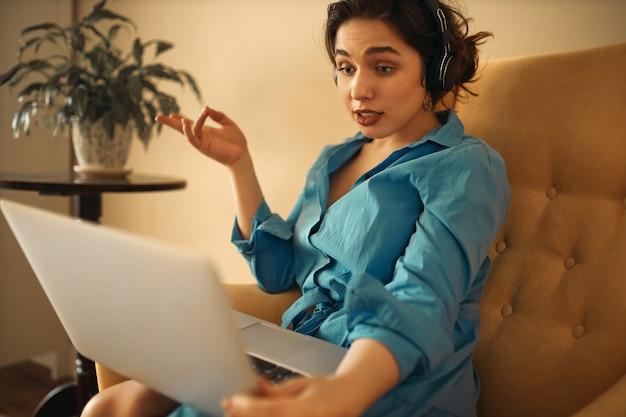 Stylowe, pewne siebie słuchawki młodej kobiety siedzącej na kanapie z laptopem uczestniczącej w grupowym spotkaniu biznesowym online za pomocą czatu konferencyjnego za pomocą kamery internetowej, gestykulującej emocjonalnie, burzy mózgów z kolegami