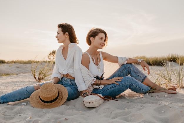Stylowe piękne kobiety na wakacjach na plaży, w stylu bohemy, dobra zabawa