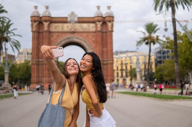 Stylowe podróżniczki robiące selfie w mieście