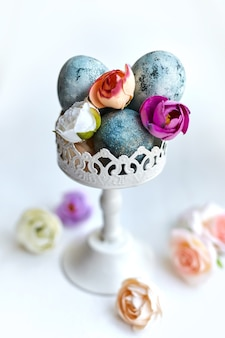 Stylowe, pomalowane na niebiesko jajka w wazonie vintage z ozdobnymi kwiatami z tkaniny. piękny kwiatowy stół na życzenia wielkanocne z selektywną ostrością.