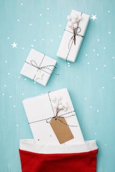 Stylowe prezenty na boże narodzenie lub nowy rok leżące na niebieskim tle, pokryte srebrnymi gwiazdkami