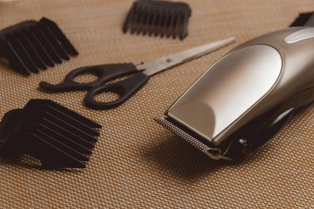 Stylowe profesjonalne maszynki do strzyżenia włosów, akcesoria na brązowym tle