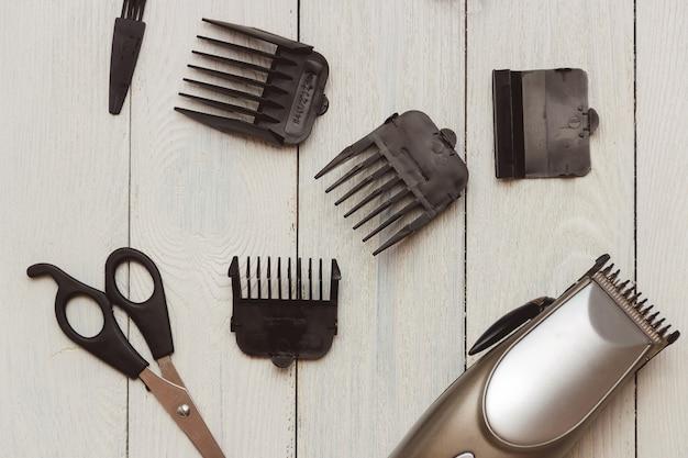 Stylowe profesjonalne maszynki do strzyżenia włosów, akcesoria na drewnianym stole