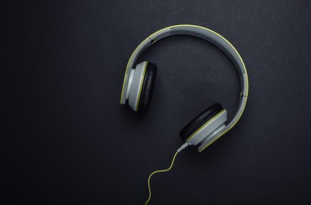 Stylowe przewodowe słuchawki stereo na czarnej powierzchni