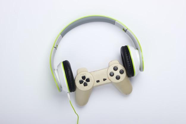 Stylowe przewodowe słuchawki stereo z gamepadem na białej powierzchni