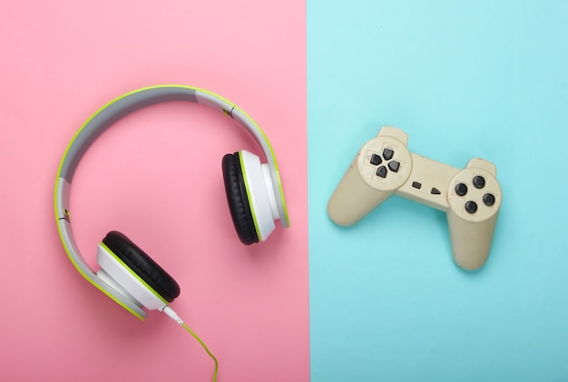 Stylowe przewodowe słuchawki stereo z gamepadem na różowo-niebieskiej powierzchni