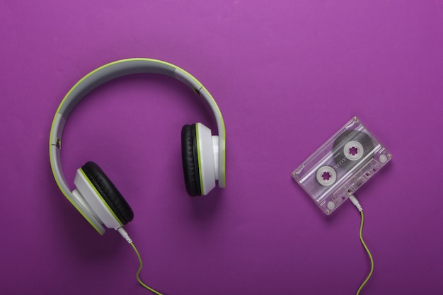 Stylowe przewodowe słuchawki stereo z kasetą audio na fioletowej powierzchni