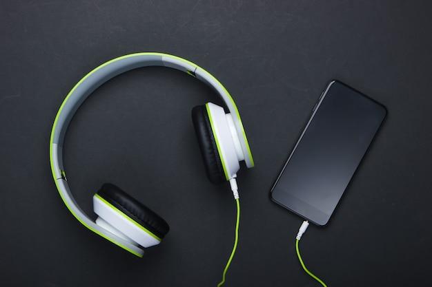 Stylowe przewodowe słuchawki stereo ze smartfonem na czarnej powierzchni