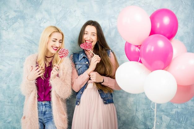 Stylowe przyjaciółki bawiące się cukierkami i balonami na niebieskim tle ściany