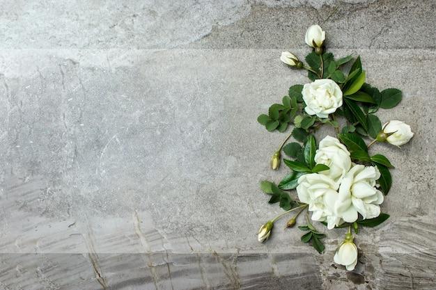 Stylowe róże na płasko. białe róże granicy na pastelowym szarym tle z miejscem na tekst.