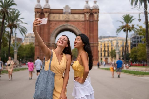 Stylowe, różnorodne dziewczyny robią sobie selfie w mieście
