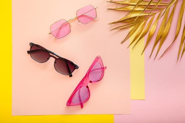Stylowe różowe okulary przeciwsłoneczne na kolorowym tle lata ze złotymi liśćmi palmowymi. modne modne okulary optyczne, kolorowe okulary przeciwsłoneczne. widok z góry płaski układanie.