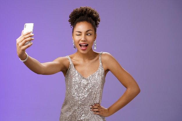 Stylowe sassy african american b-day girl biorąc selfie nowa elegancka srebrna błyszcząca sukienka przedłużyć ramię trzymając smartfon pozowanie mrugając ekran bawi się dobrze uśmiechając się szeroko, niebieskim tle.