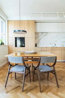 Stylowe skandynawskie wnętrze kuchni i jadalni z rodzinnym stołem i krzesłami oraz akcesoriami