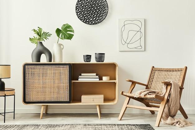 Stylowe, skandynawskie wnętrze nowoczesnego salonu z drewnianą komodą, designerskim fotelem, dywanem, liściem w wazonie, lampą stołową i akcesoriami osobistymi w niepowtarzalnym wystroju domu.