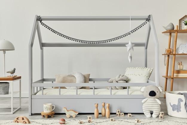 Stylowe skandynawskie wnętrze pokoju dziecięcego z kreatywnym drewnianym łóżkiem, stolikiem kawowym, lampą, drewnianą półką, pluszowymi i drewnianymi zabawkami oraz wiszącymi dekoracjami tekstylnymi. szare ściany, dywan na podłodze. szablon.