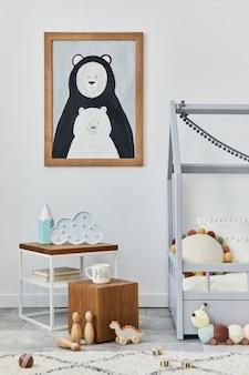 Stylowe skandynawskie wnętrze pokoju dziecięcego z makietą ramy plakatowej, kreatywnym łóżkiem, drewnianą kostką, pluszowymi i drewnianymi zabawkami oraz wiszącymi dekoracjami tekstylnymi. szara ściana, dywan na podłodze. szablon.