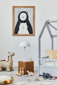 Stylowe skandynawskie wnętrze pokoju dziecięcego z makietą ramy plakatowej, kreatywnym łóżkiem, drewnianą kostką, pluszowymi i drewnianymi zabawkami oraz wiszącymi dekoracjami tekstylnymi. szare ściany. szablon.
