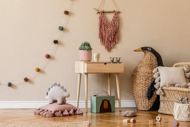 Stylowe, skandynawskie wnętrze pokoju dziecięcego z naturalnymi zabawkami, wiszącymi dekoracjami, designerskimi meblami, pluszowymi zwierzakami, pluszowymi misiami i dodatkami. beżowe ściany. projekt wnętrza pokoju dziecięcego.