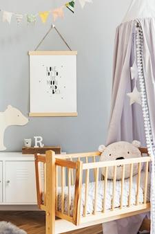 Stylowe skandynawskie wnętrze przedszkola z wiszącym plakatem makiety, szarym baldachimem w gwiazdki i białą półką z poduszką w chmurkę, naturalnym koszem i akcesoriami dla dzieci. szare tło ściany.