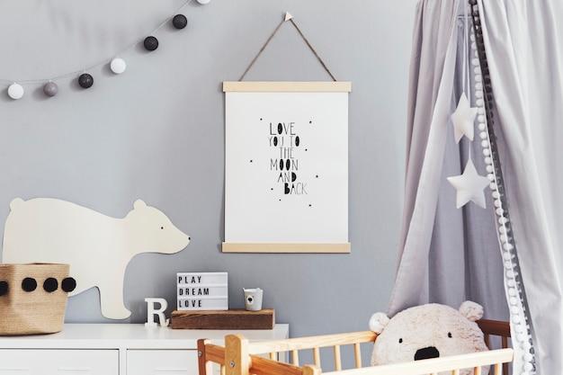 Stylowe skandynawskie wnętrze przedszkola z wiszącym plakatem, szarym baldachimem w gwiazdki i białą półką z poduszką chmurki, naturalnym koszykiem i akcesoriami dla dzieci