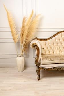 Stylowe skandynawskie wnętrze salonu nowoczesnego mieszkania z trawą pampasową i przytulną sofą w jasnych kolorach. kawałek beżowej klasycznej sofy i trawy pampasowej w wazonie. trawa pampasowa. wystrój domu.