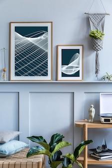 Stylowe skandynawskie wnętrze salonu z designerskimi szezlongami, drewnianą konsolą, roślinami, książkami, dekoracją, ramkami na plakaty na półce i eleganckimi dodatkami w nowoczesnym wystroju domu.