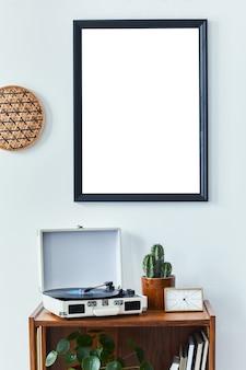Stylowe skandynawskie wnętrze salonu z komodą retro, czarną makietową ramą plakatową, zegarem, dekoracją kaktusów, książką i osobistymi akcesoriami w wystroju domu. szablon