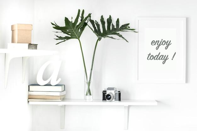 Stylowe skandynawskie wnętrze z białą półką białą makieta plakatowa rama książki liście aparatu