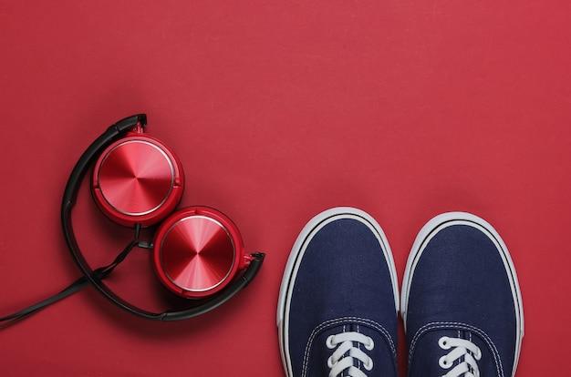 Stylowe słuchawki starej szkoły trampki na czerwonym tle