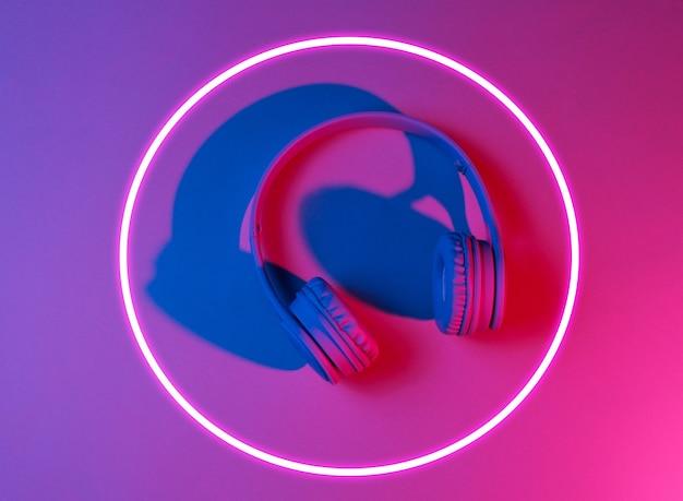 Stylowe słuchawki. syntezatorowa fala i retrowave z lat 80-tych, świecące koło, futurystyczna estetyka