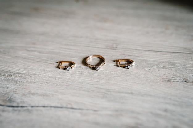 Stylowe srebrne kolczyki, złote pierścienie na stole
