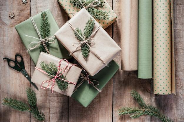 Stylowe świąteczne pudełko owinięte i ozdobione naturalnymi materiałami: papierem z recyklingu, liną jutową i gałęziami jodły
