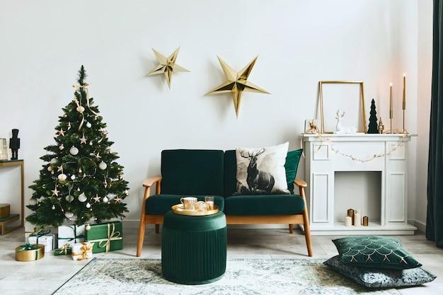 Stylowe świąteczne wnętrze salonu z zieloną sofą, białym kominem, choinką i wieńcem, gwiazdami, prezentami i dekoracją. czas dla rodziny. szablon.