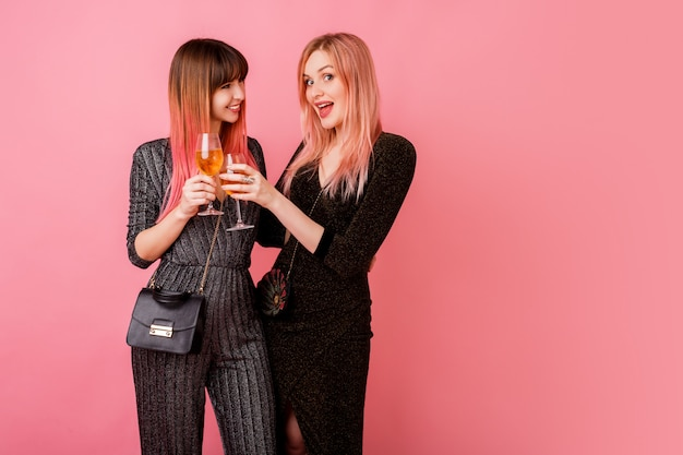 Stylowe świętujące kobiety w imprezowej sukience piją szampana i świetnie się razem bawią