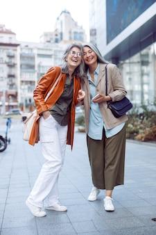 Stylowe szczęśliwe starsze kobiety stoją na nowoczesnej ulicy miasta w jesienny dzień