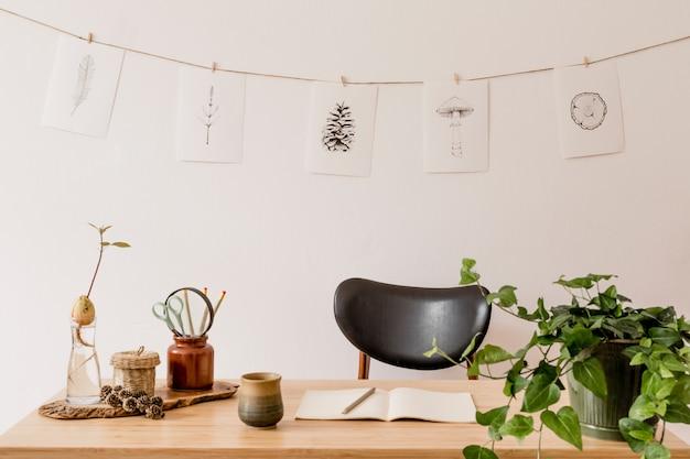 Stylowe wnętrze domowego biura z drewnianym biurkiem, leśnymi dodatkami, rośliną awokado, bambusową półką, roślinami i dekoracją z rattanu. neutralny wystrój domu.
