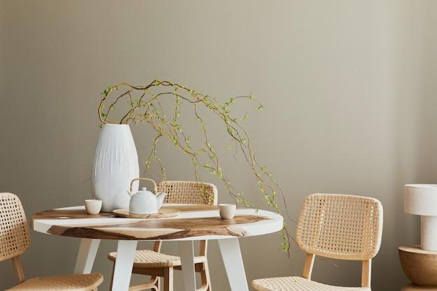 Stylowe wnętrze jadalni w przytulnym domu z przestrzenią do kopiowania, designerskimi krzesłami, rodzinnym stołem, czajnikiem, filiżankami, dekoracją i eleganckimi akcesoriami osobistymi w nowoczesnym wystroju domu.