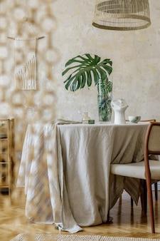 Stylowe wnętrze jadalni z drewnianym stołem, designerskimi krzesłami, rattanową lampą wiszącą, wiosennymi kwiatami w wazonie, pięknymi talerzami, roślinami i elegancką dekoracją. koncepcja wabi sabi...