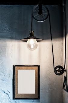 Stylowe wnętrze loftu, lampa edisson, drewniana ramka ze zdjęciem na ścianie z pustym miejscem na napis.