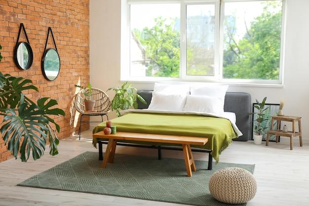 Stylowe wnętrze nowoczesnej sypialni z lustrami i roślinami doniczkowymi