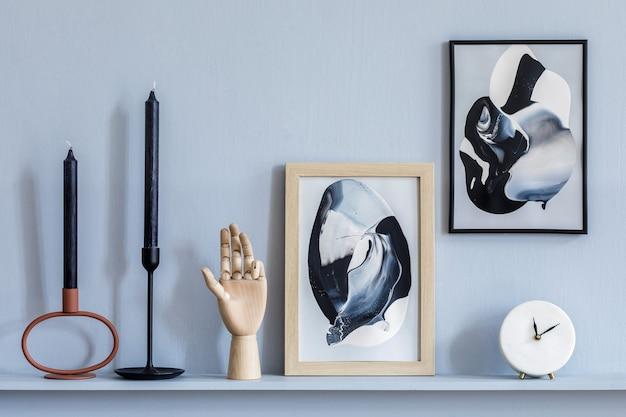 Stylowe wnętrze salonu w eleganckim apartamencie z dwiema ramkami, białym zegarem, świecami, drewnianą wskazówką, szarą boazerią i eleganckimi dodatkami na półce w nowoczesnej home staging