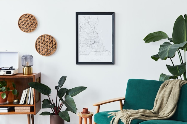Stylowe wnętrze salonu z designerską drewnianą półką, aksamitną sofą, dużą ilością roślin, mapą plakatową, magnetofonem winylowym, książką i akcesoriami osobistymi w stylu vintage home decor.