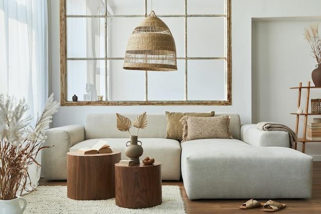 Stylowe wnętrze salonu z designerską sofą modułową, meblami, drewnianym stolikiem kawowym, dekoracją rattanową, lampą wiszącą, poduszką, suszonymi kwiatami i eleganckimi dodatkami w nowoczesnym wystroju domu.