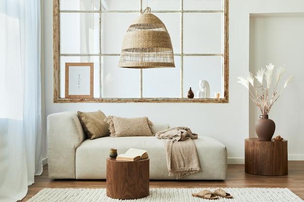 Stylowe wnętrze salonu z designerską sofą modułową, meblami, drewnianym stolikiem kawowym, dekoracją rattanową, ramą na zdjęcie, poduszką, suszonymi kwiatami i eleganckimi dodatkami w nowoczesnym wystroju domu.