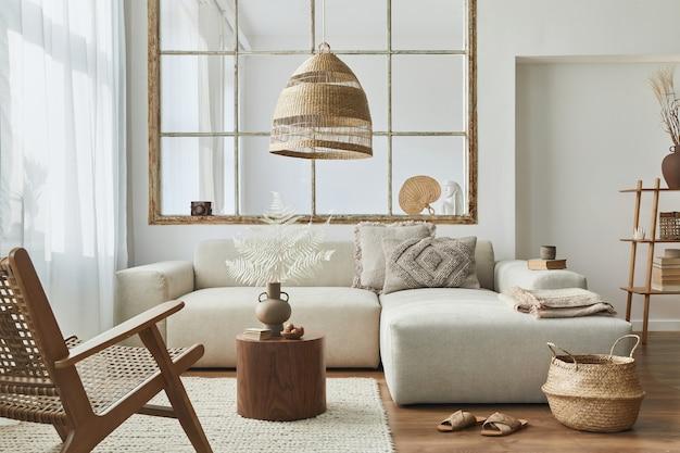 Stylowe wnętrze salonu z designerską sofą modułową, meblami, drewnianym stolikiem kawowym, dekoracją z rattanu.