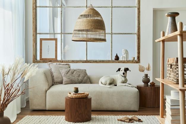 Stylowe wnętrze salonu z designerską sofą modułową, meblami, stolikiem kawowym, dekoracją rattanową, suszonymi kwiatami i eleganckimi dodatkami w nowoczesnym wystroju domu. piękny pies leżący na kanapie.